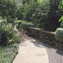walkway stepping stones and raised planter with rock wall